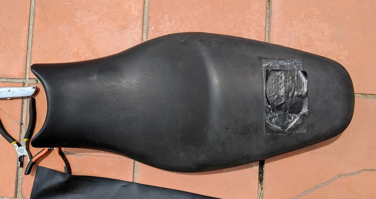 Original Ninja 650 motorcycle seat with patch and tools ready for re-upholstering