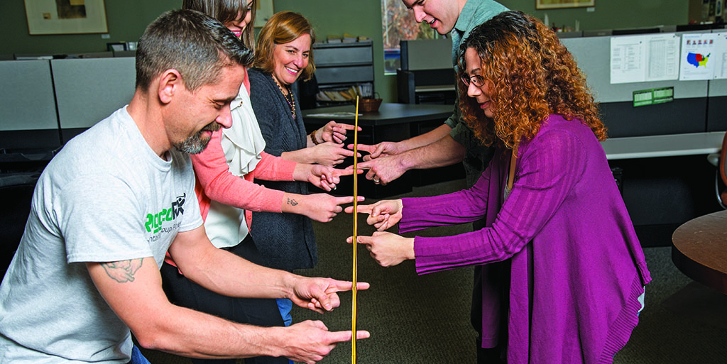 Helium stick exercise - everyone has to keep touching the stick