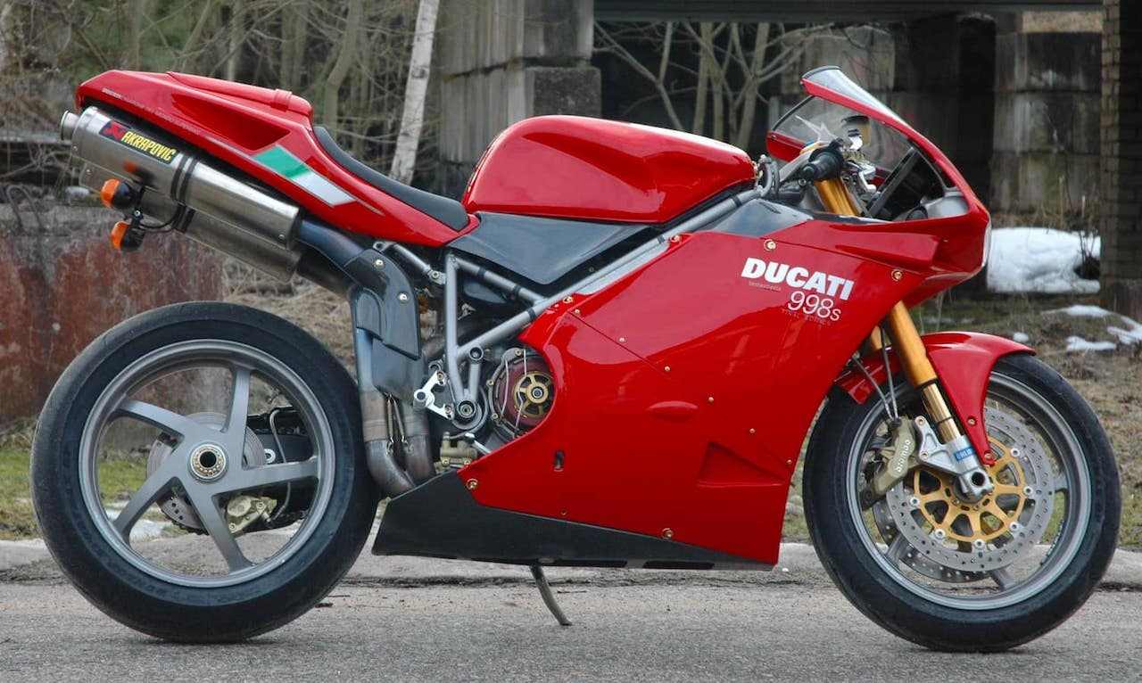 The Ducati 998S with lightweight Marchesini wheels and gold Öhlins front forks, trees in background.