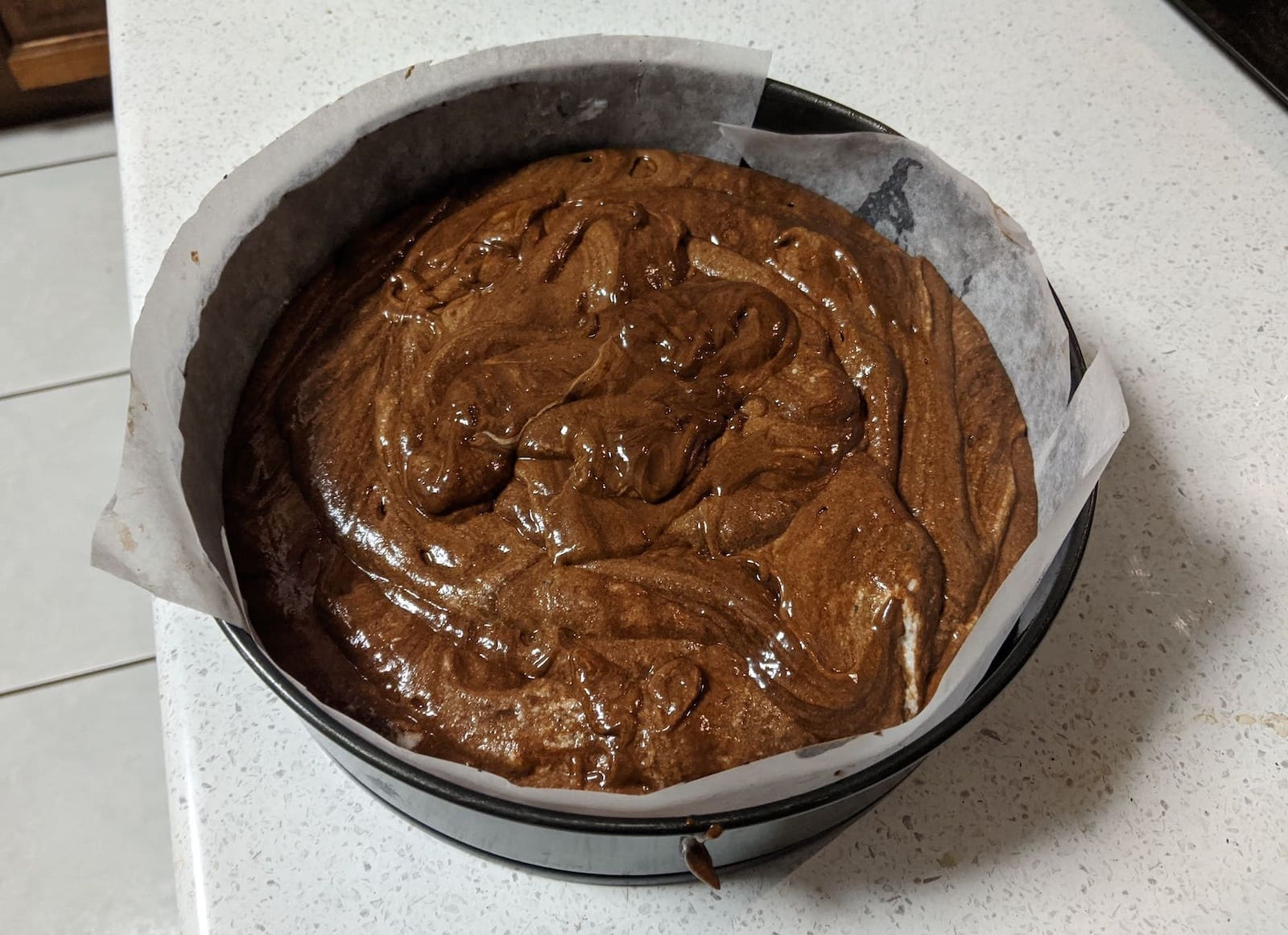 chocolate mousse poured into a tin, ready to become cake