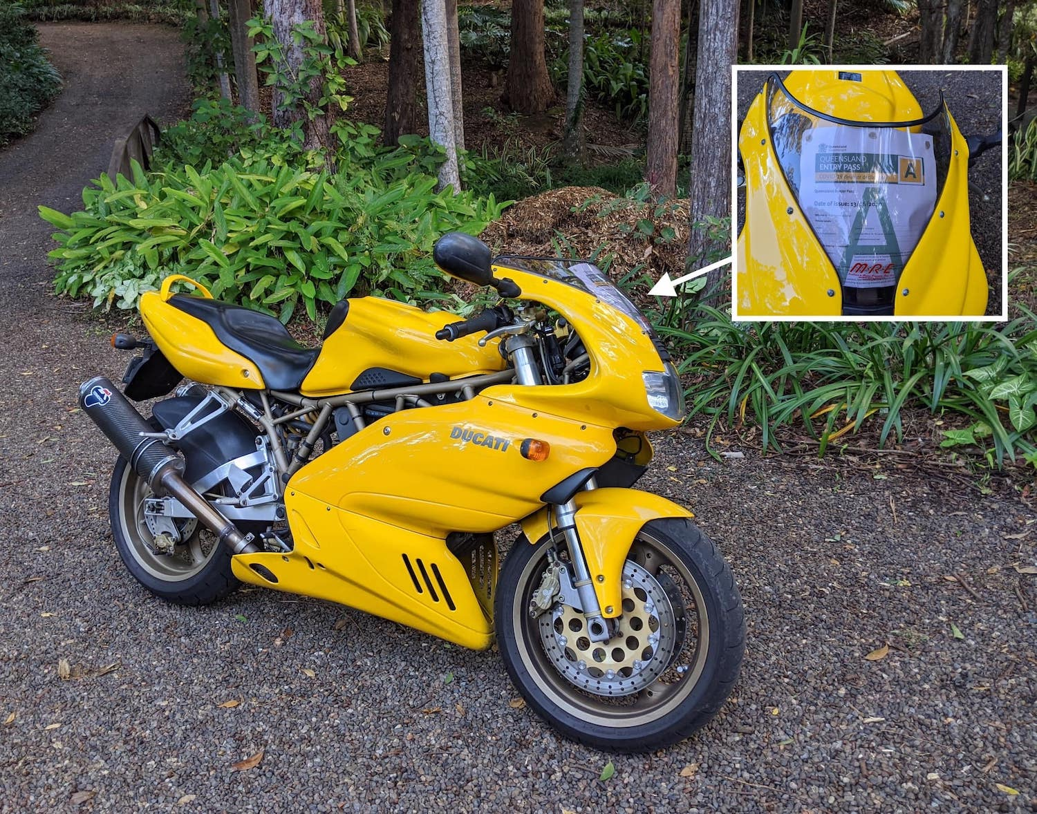 Yellow Ducati motorcycle with Queensland COVID-19 entry pass