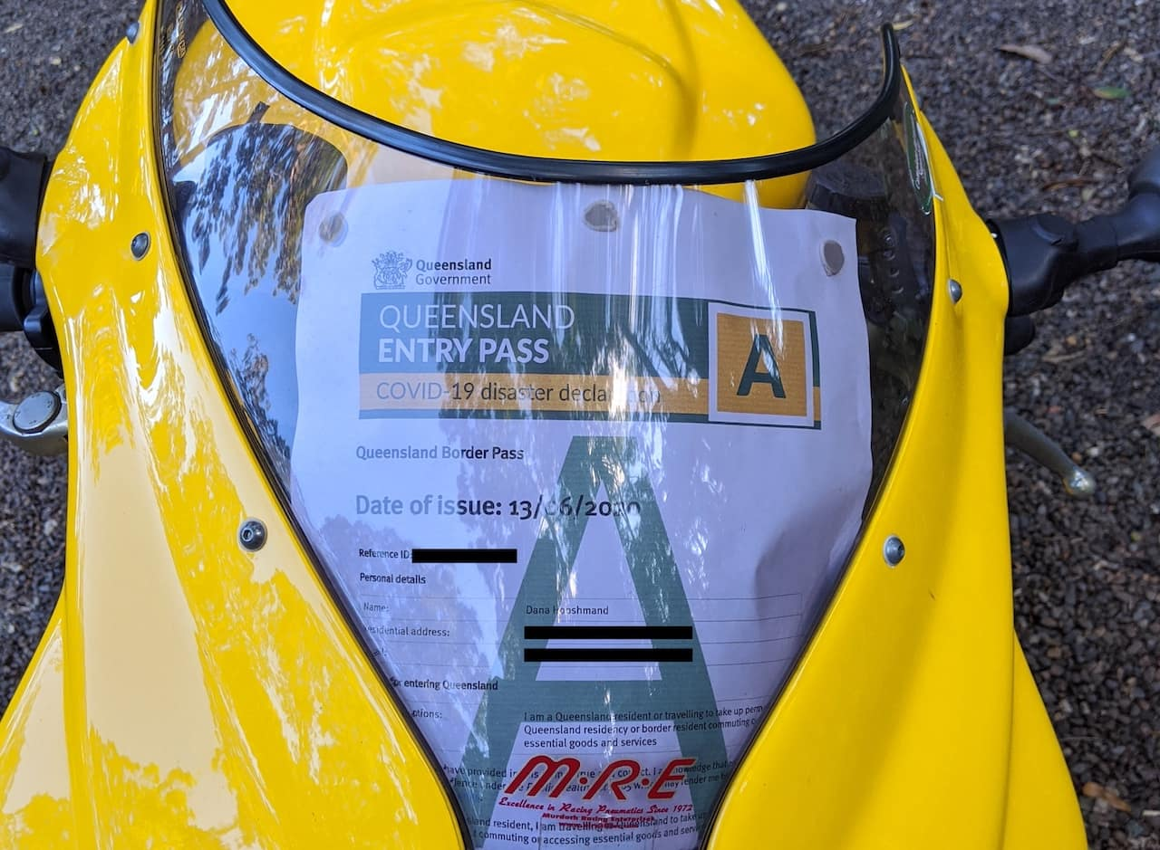 Queensland COVID-19 disaster declaration entry pass under motorcycle windshield
